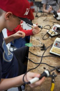 Closeup of Lincoln Middle School student working on electronics